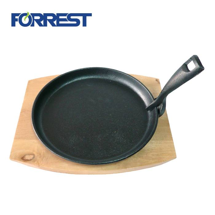 Cast iron skillet sizzling plate with wooden base