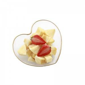 Clear heart-shaped bowl of fruit, candy and vegetable salad